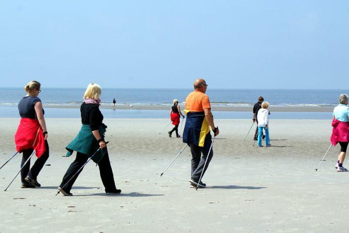Ľudia prechádzajúci sa po pláži si vychutnávajú krásu nordic walkingu.